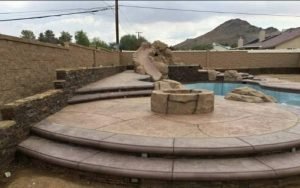 water slide pool with a fire pit - pool construction by SilverRock Pools